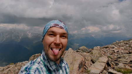 grimacing : Man takes camera in the hand on the mountain and show tongue
