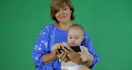 удивленный : 4k - Mom and baby are watching something funny on her smartphone Стоковые видеозаписи