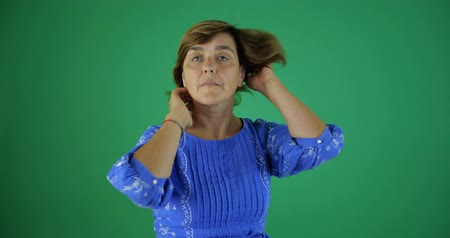 中世の : 4k - An elegant woman straightens her hair on the green screen in studio