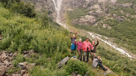 extreme weather : 4k - Expedition of young tourists waving near mountain waterfall, aerial action Stock Footage