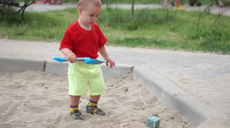 sandpit : A little boy playing with a shovel in the sandbox in slow motion
