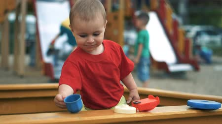 sandpit : A small boy is standing in the sandbox and playing with a toy cup in slow motion Stock Footage