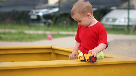 sandpit : A little boy is standing in the sandbox, playing with a broken car, slow motion
