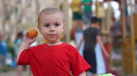 atmak : A small boy throws away a mandarin like a ball on the playground in slow motion