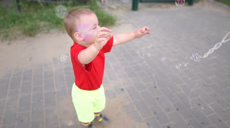 catch : A small boy catches soap bubbles outdoors on a sunny summer day in slow motion