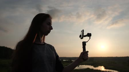 stabilizátor : Pretty girl shoots video on the phone with a stabilizer at sunset, slow motion Stock mozgókép