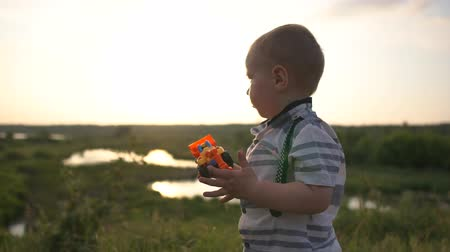 játék : A cute elegant boy plays with a tractor at sunset in slow motion