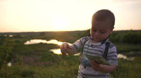доллар : A little boy was given several hundred dollar bills on nature in slow motion Стоковые видеозаписи