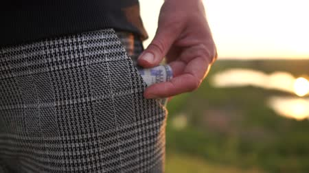 zakgeld : The girl pulled out of her pants pocket a stack of dollar bills in slow motion