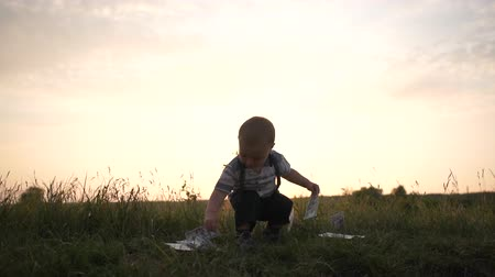 piyango : A joyful boy raises dollar bills from the grass and throws it in slow motion