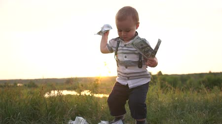 raises : Happy boy raises money from the grass and throws the dollar bills in slow motion