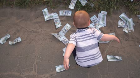 moltitudine : A little boy is standing on the road among a multitude of scattered banknotes Filmati Stock