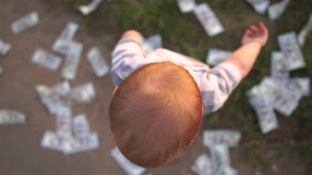 nape : A small child throws hundred dollar bills around him in slow motion
