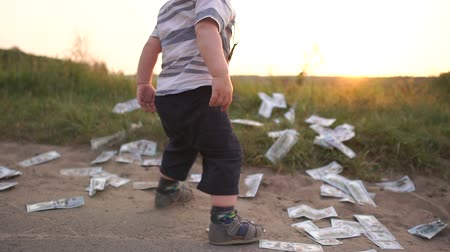 euforia : Cute boy happily throws a huge stack of dollar bills to the ground, slow motion