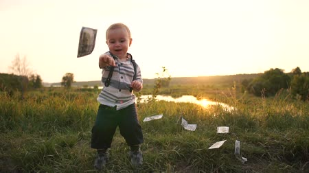 lotterie : Happy boy raises money from the grass and throws the dollar bills in slow motion