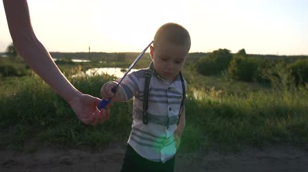 zöld fű : A joyful small boy waving a bubble wand on the field in slow motion