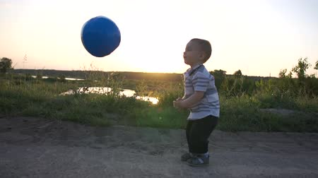volleyball : A little boy like a volleyball player beats off a ball in slow motion outdoors