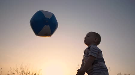 volleyball players : A little boy beats off a ball like a volleyball player at sunset in slow motion Stock Footage