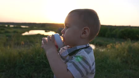 mamilo : A cute boy drinks a compote from a baby bottle outdoors in slow motion