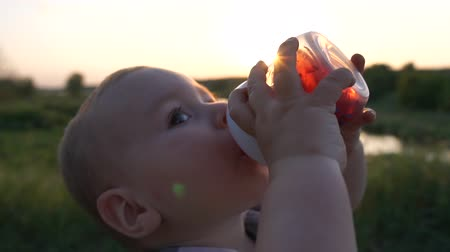 frasco pequeno : A little boy drinks a drink from a baby bottle in the field in slow motion