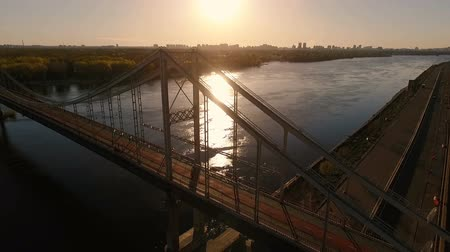 подвесной : Aerial shot of a famous suspension cable bridge in Kyiv at splendid sunset in summer