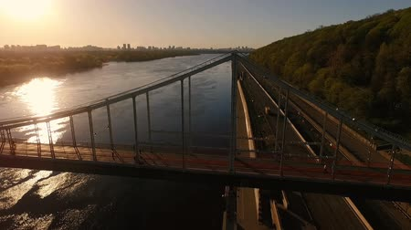 süspansiyon : Aerial shot of a beautiful suspension cable bridge in Kyiv at golden sunset in summer Stok Video