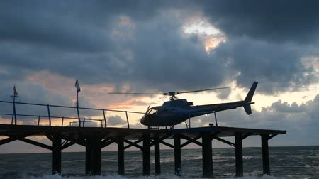 splendid : Modern helicopter standing on a wodden pier in the Black Sea shore in slo-mo Stock Footage