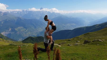 a genoux : Young woman stepping on her mans knee in Georgian Mountains in summer in slo-mo