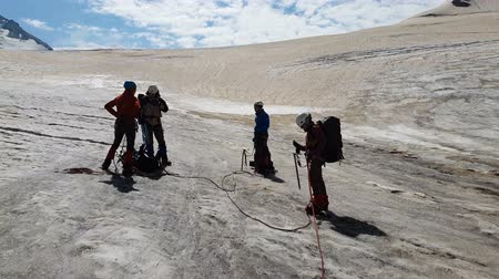 machado : Four climbers standing with ice axes in Georia mountains in summer in slo-mo