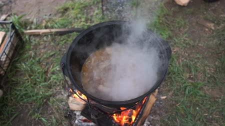 kaynatmak : Sliced pieces of meat boiling in a large pot with soup outdoors in slo-mo