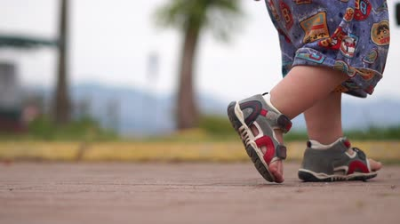 szandál : Legs in sandals of a little boy walking on the road in slow motion