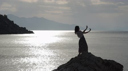 danseuse orientale : The beautiful sexy girl dancing on a rock above the sea in slow motion at sunset