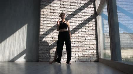 アクロバティック : Blonde girl dancing contemp in spacious studio with French windows in slo-mo 動画素材