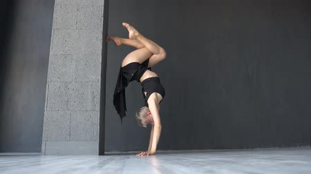 dita incrociate : Elegant blonde girl doing eagle-stand while dancing contemporary in studio in slo-mo