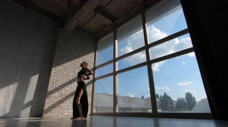 interior : Beautiful blonde girl dancing and spinning at a window at sunset in studio in slo-mo