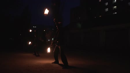 pessoal : Female and male show people in black suits spinning fireballs at night in slo-mo Vídeos