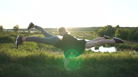 mond : Strong blond man does a handstand with a girl keeping legs oppositely at sunset in slo-mo