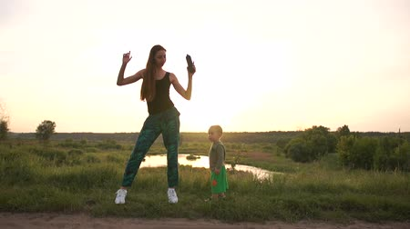 hangszórók : Happy mother dancing with her toddler at small lake at sunset in slo-mo