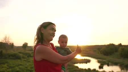 bob hairstyle : Happy woman dancing with a little kid at small lake at sunset in slo-mo