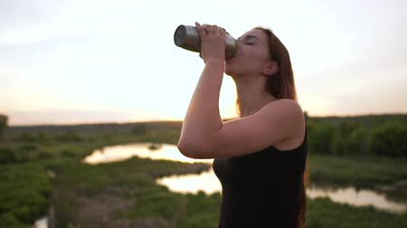 matraz : Happy young woman drinking tea from a flask at pool at sunset in slo-mo