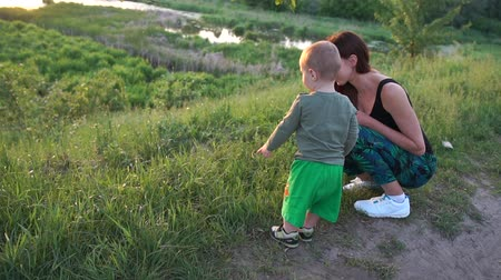 sağlam : Cheery mother sitting and chatting with her toddler at lake at sunset in slo-mo