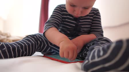 mobile game : Baby is enthusiastically played with a smartphone sitting on a bed, slow motion Stock Footage