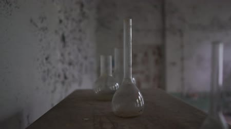 впечатляющий : Round medicine flasks and dirty tubes are on a shabby table in old hall in slo-mo