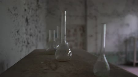 fazla : Round chemical flasks and grubby tubes are on a dirty table in old hall in slo-mo