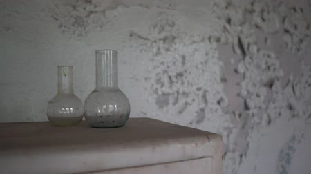 chernobyl : Polluted chemical flasks and radiactive tubes are on an old cabin in room in slo-mo