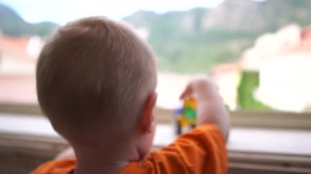 sandpit : A small boy standing near the window and playing with the truck in slow motion Stock Footage