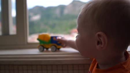 sill : A toddler standing near the window and playing with the truck in slow motion