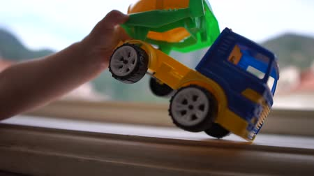 sandpit : A cute boy standing near the window and playing with the truck in slow motion
