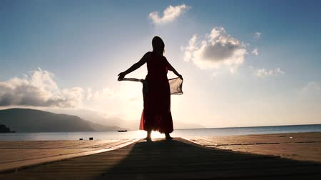 horizont : A pretty woman with a scarf stands on the seashore at sunrise in slow motion Stock mozgókép