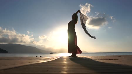 pontoon : A woman with a transparent scarf stands on the seashore at dawn, slow motion